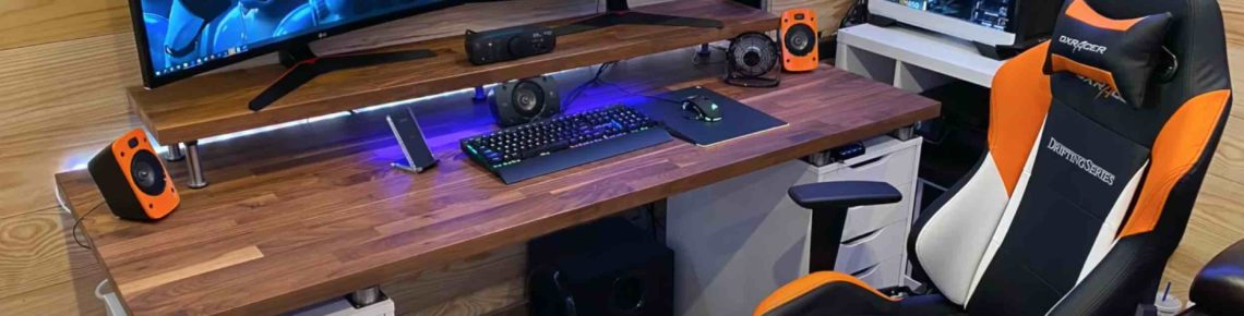 Two monitors are on the table and black gaming chair with white and orange sides