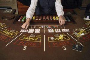 Le croupier met des cartes sur la table de baccarat