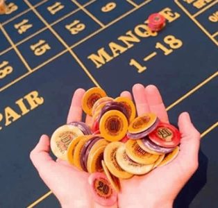 A person is holding casino chips