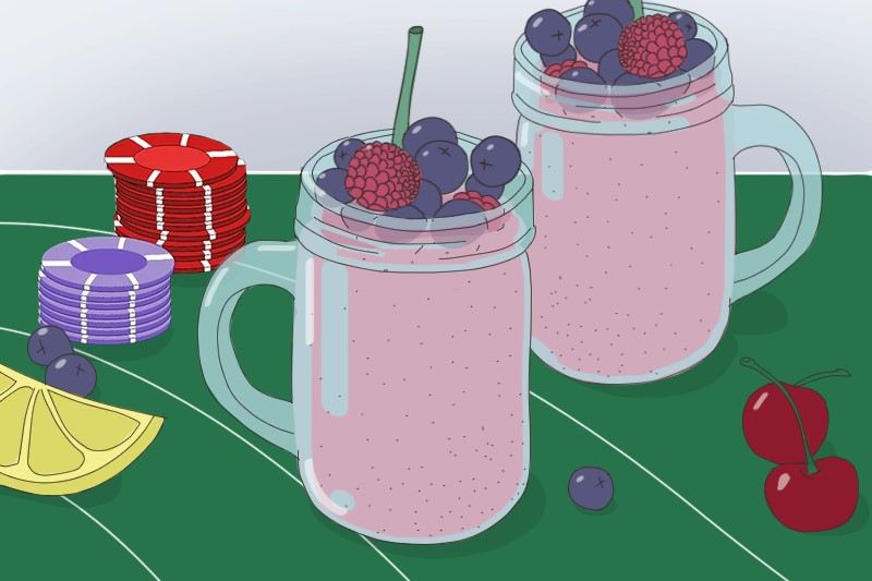 Two cups with a fruit smoothie, several berries and lemon slice are on the table