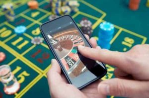 A person is playing roulette on his smartphone in front of the poker table