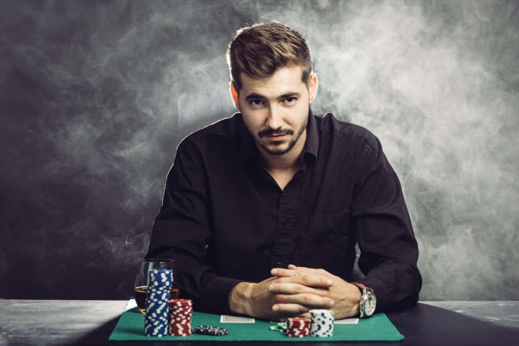A man wearing a black shirt is sitting on the poker table in a casino