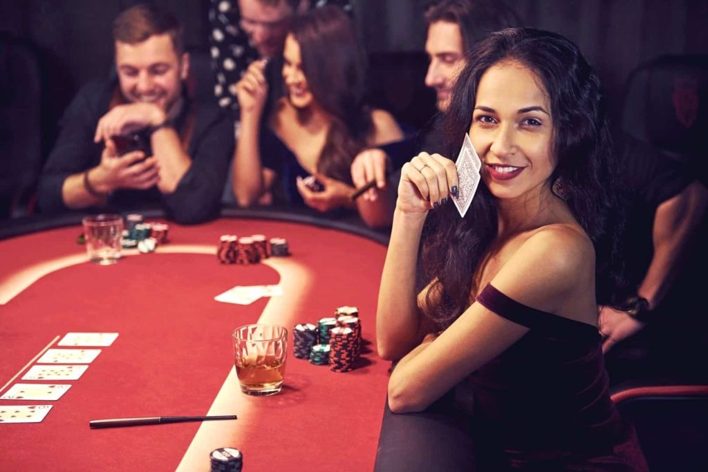 Beautiful and young woman with a group of people playing in a casino