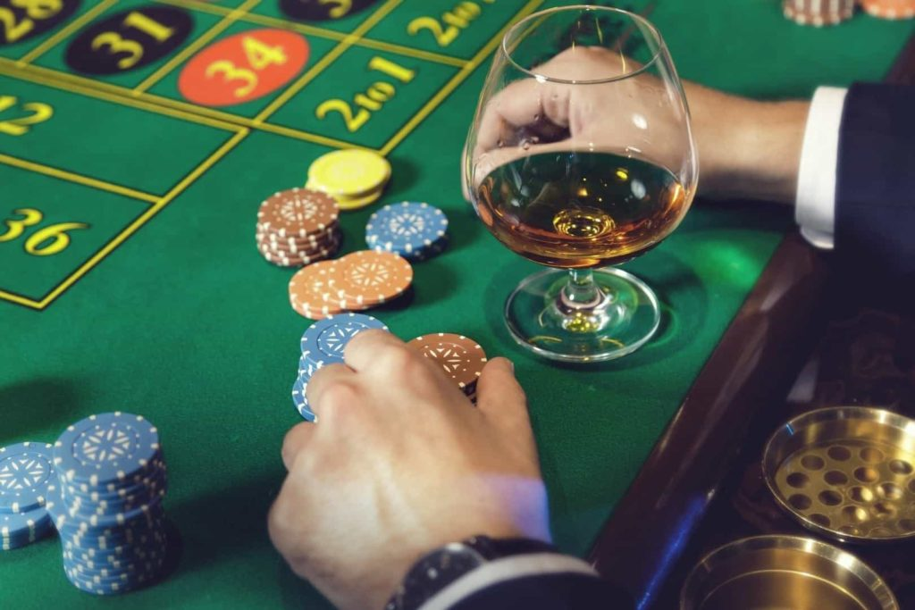 Man wearing a suit is playing roulette and drinking wine