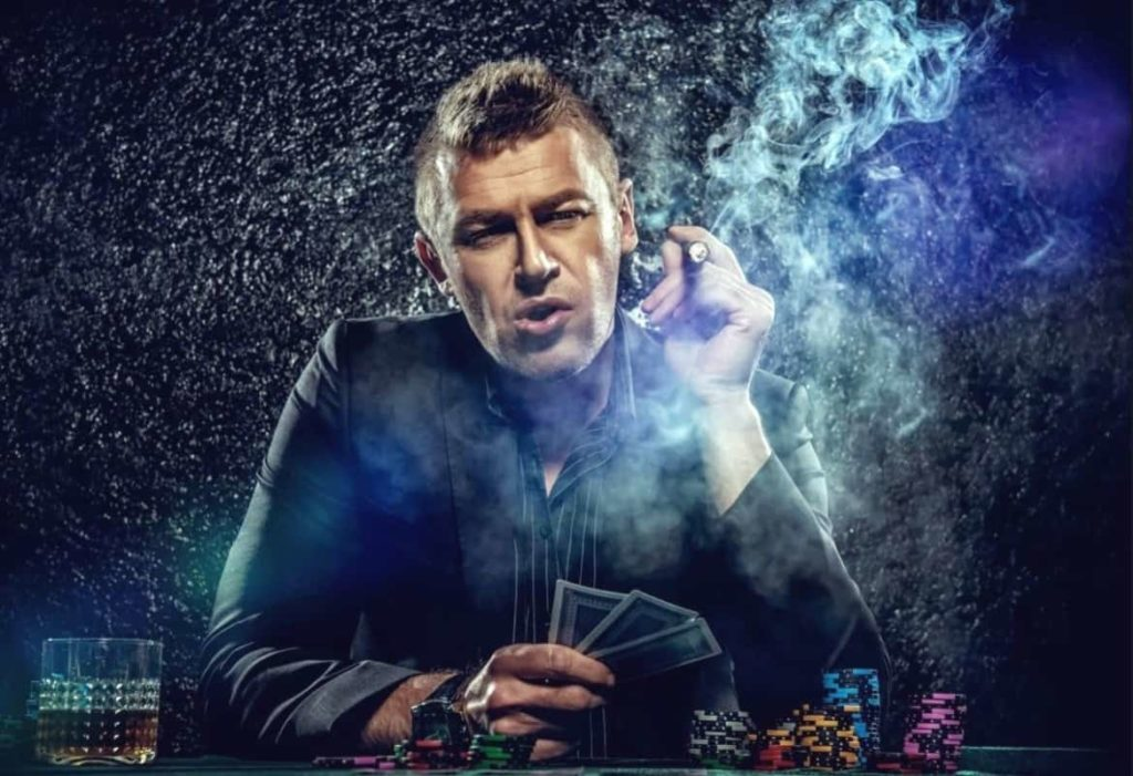 A man is playing poker and smoking a cigarette