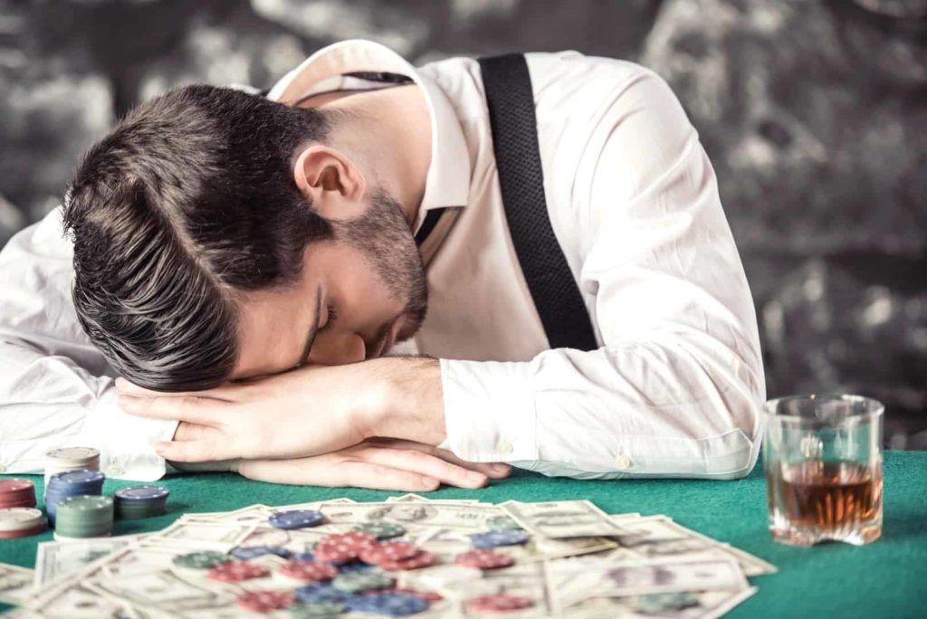 A tired and depressed player put his head on the poker table in a casino