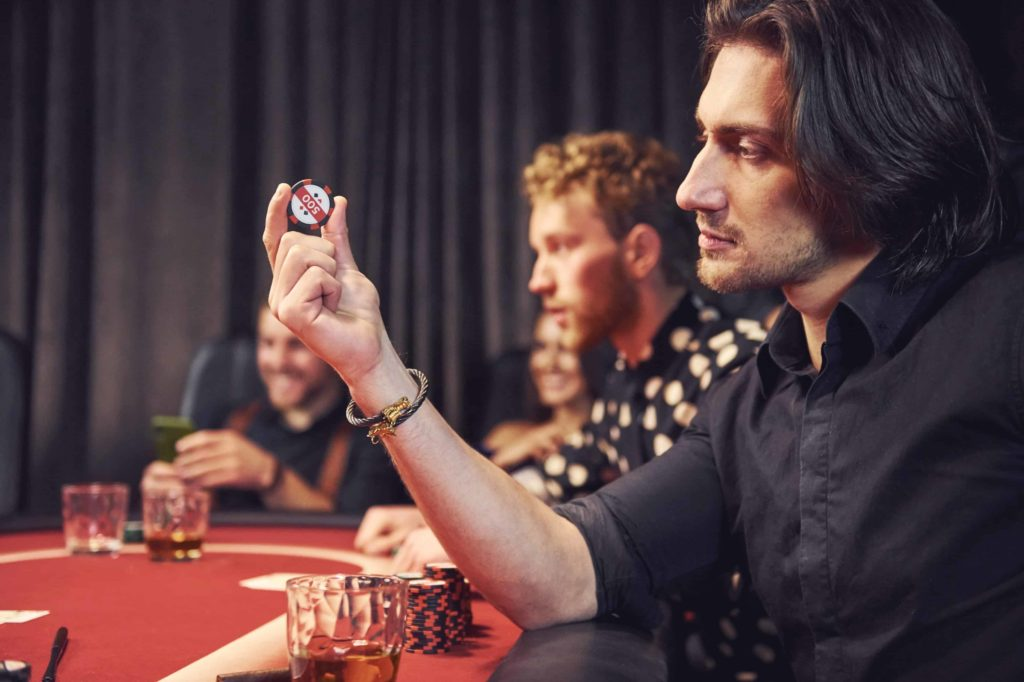 A young poker player is holding casino chips in the casino