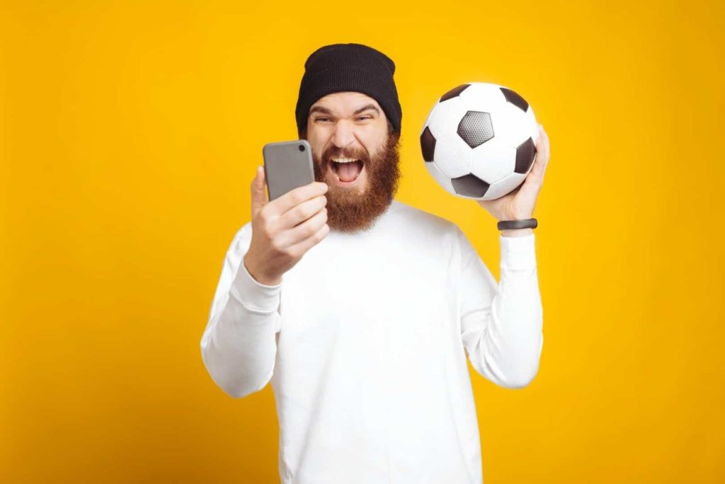 A man wearing a white sweater is holding a soccer ball and a phone to make a sport bet
