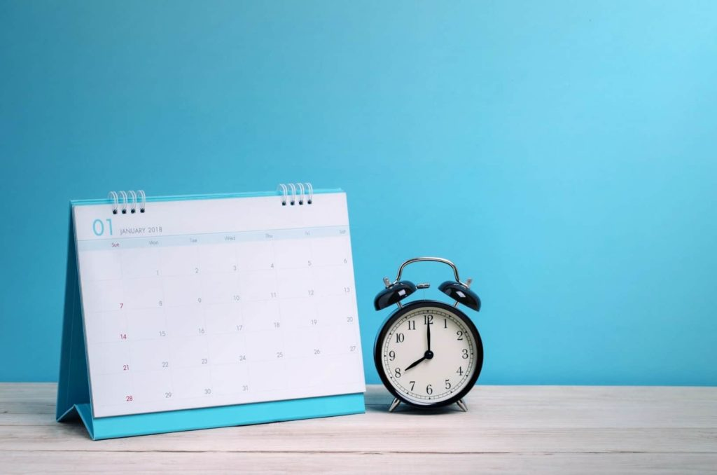 A clock and a calendar are on the table