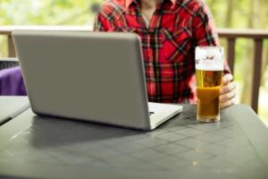 A young man is drinking beer while playing online casino games on his laptop
