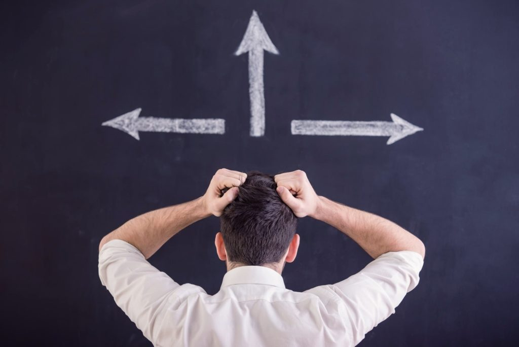 A man is looking at three different arrows and trying to make a choice
