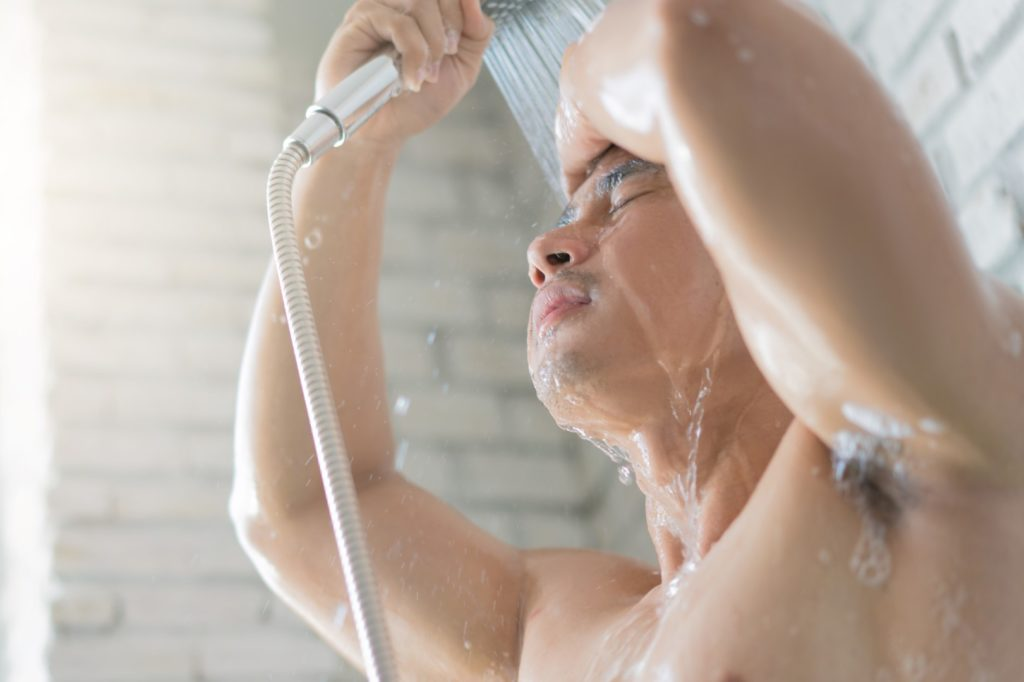 A young man is pouring water on himself in the shower