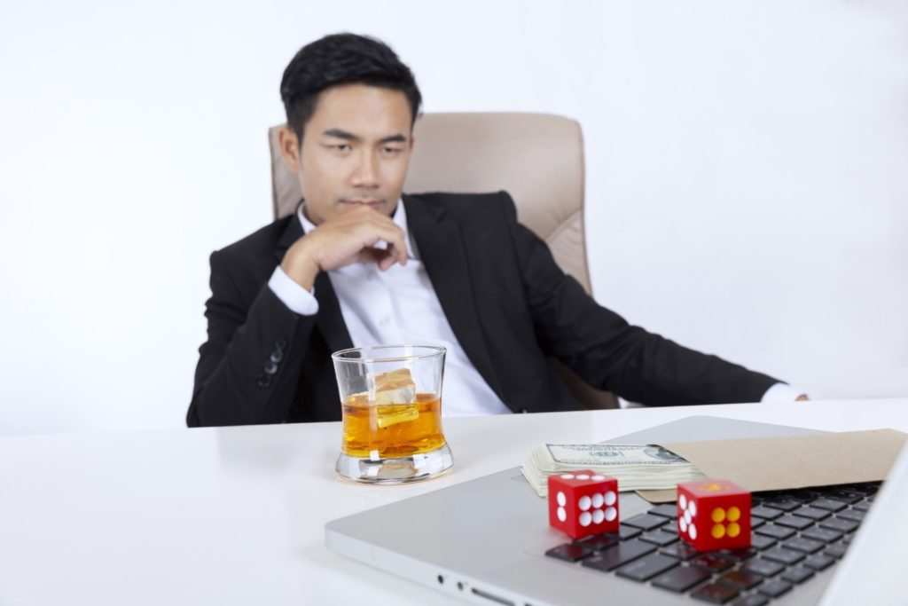 A young man is sitting in front of the laptop with dice, money, and a glass of alcohol