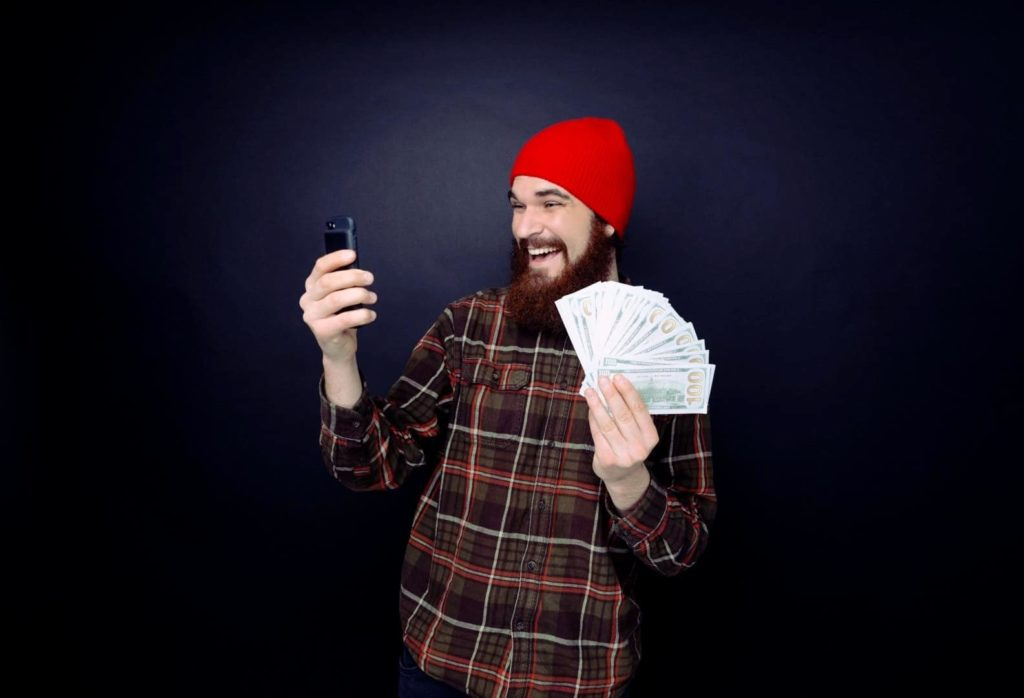 A happy young man is holding money and making bets on the phone