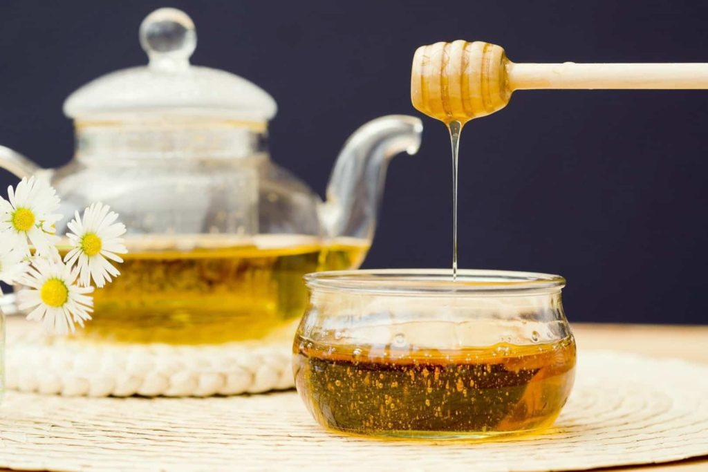 A glass teapot and a honey pot are on the table