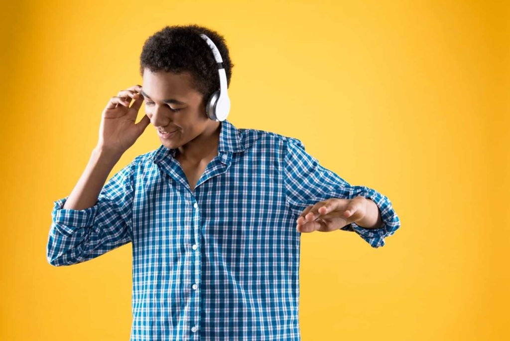 A teenager is dancing while wearing white headphones