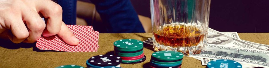 A man is holding cards while poker chips and a glass of alcohol are on the table