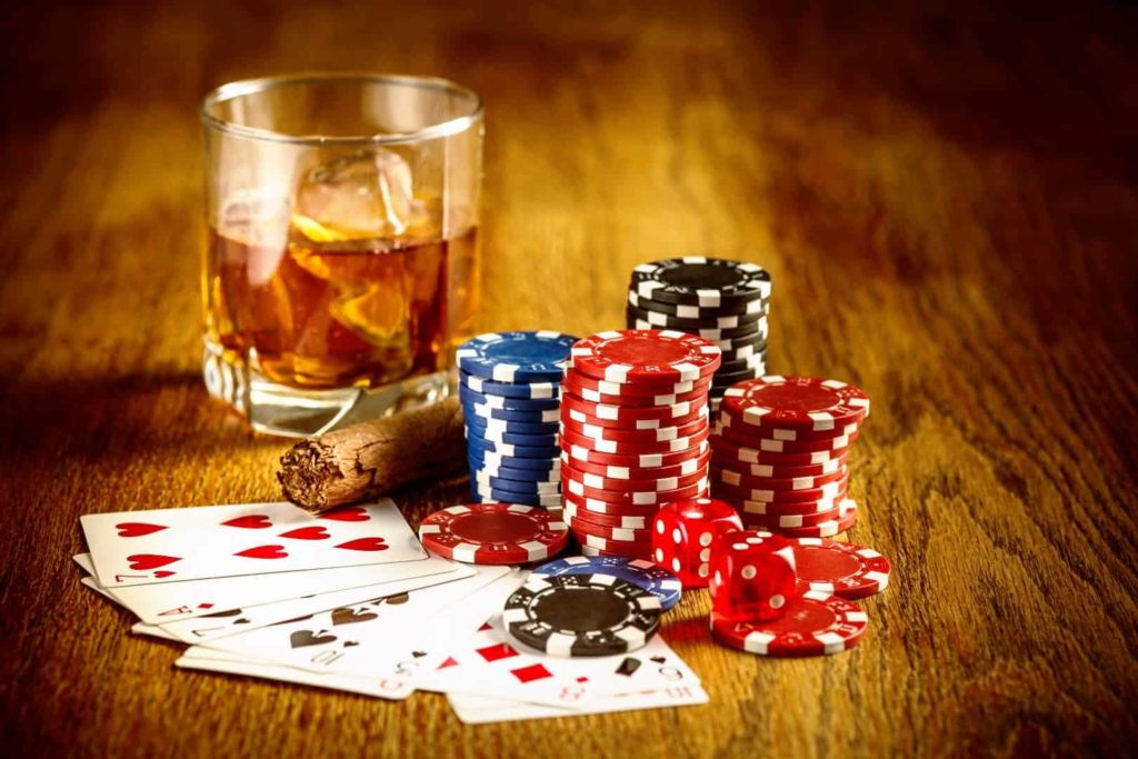 A glass of alcohol, cards, poker chips and cigarette are on the table