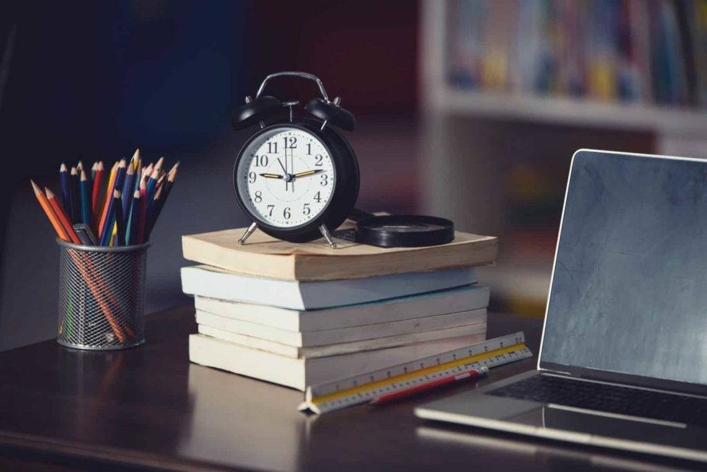 A clock is on the pile of books near the laptop and pencils