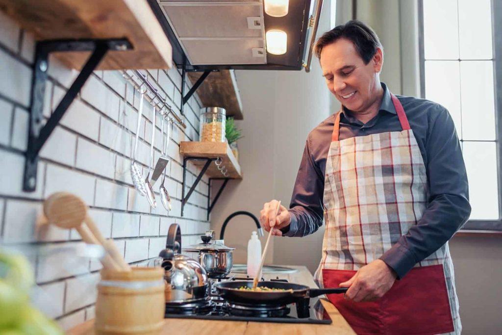 Un homme d'âge moyen porte un tablier et cuisine