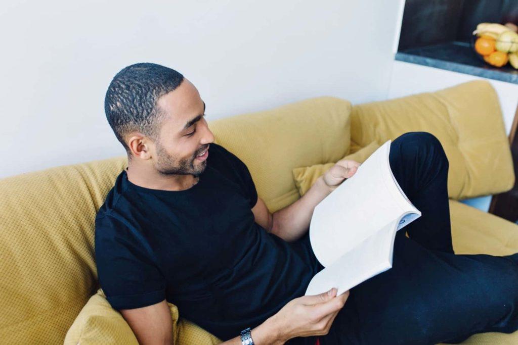 Un homme lit un livre et s'allonge sur le canapé