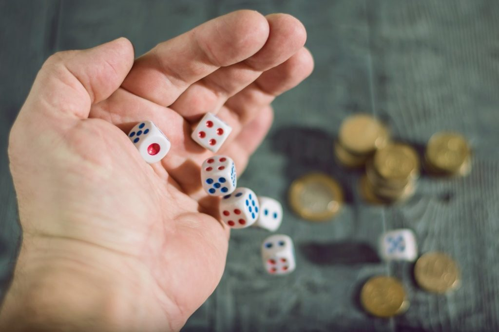 A man is throwing dice to the table with coins
