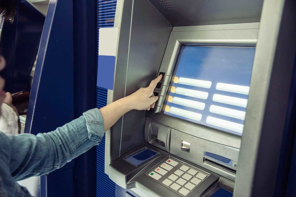 A woman is withdrawing the money from ATM