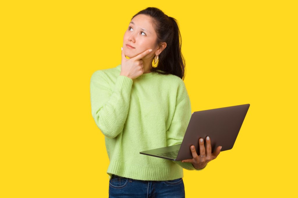 A thinking girl is touching her face while holding her laptop