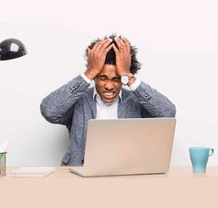 A young black man is feeling stressed and nervous sitting on the laptop