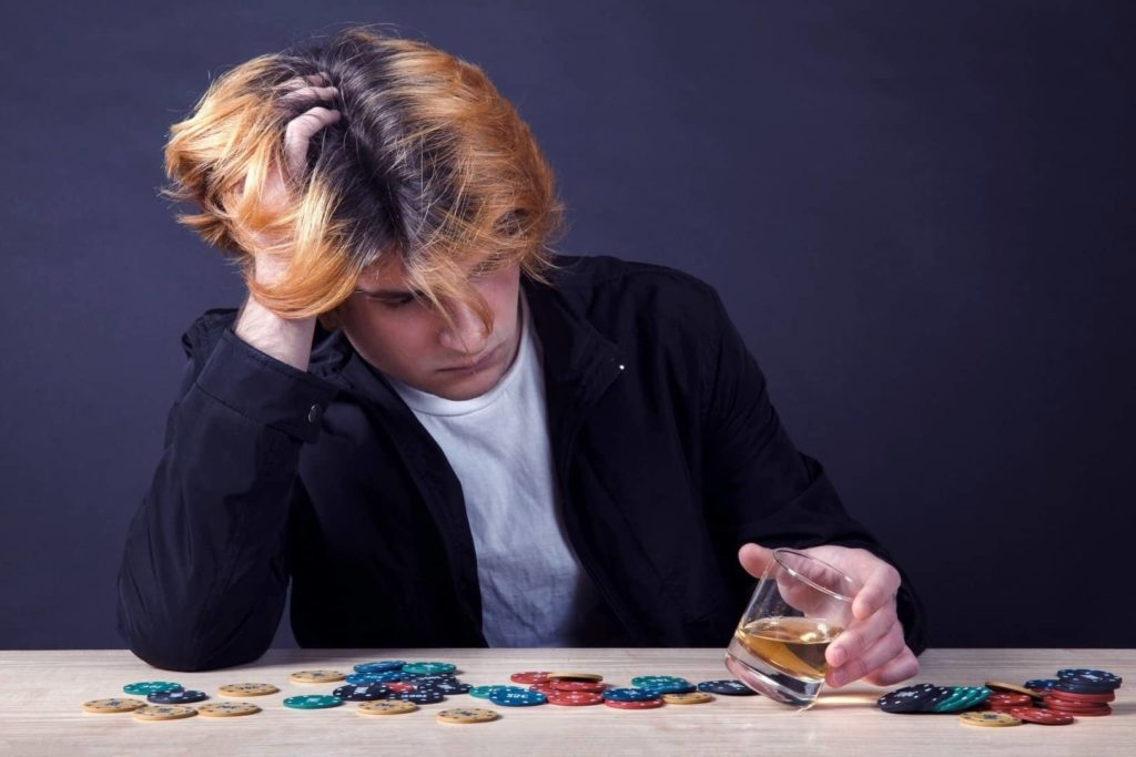 A young man is sitting on the table with poker chips and holding a glass of whiskey