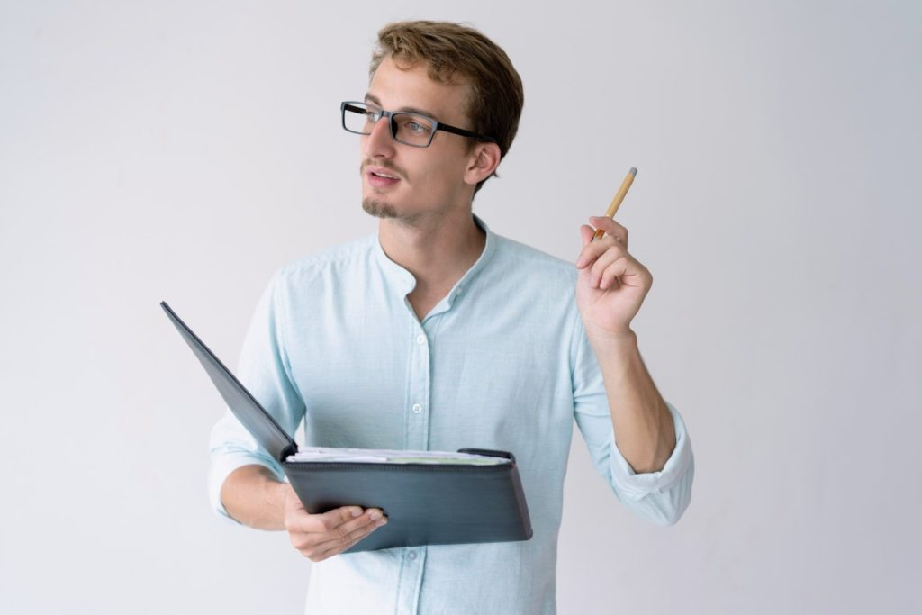 A young man wearing a blue shirt is holding a file and a pen and having an idea