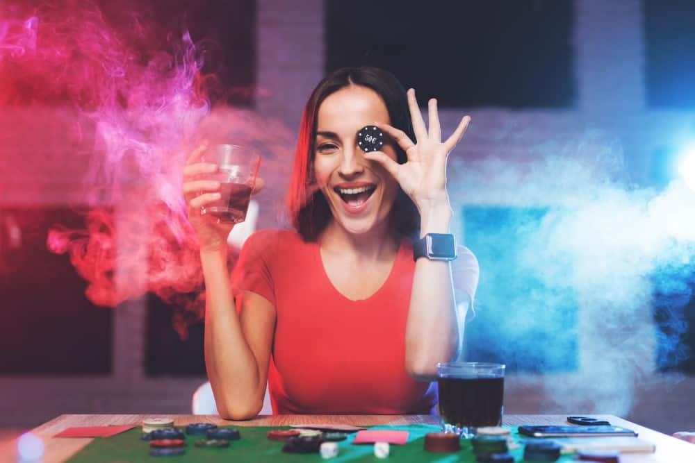 A girl wearing red t-shirt is sitting in the casino and holding a chip and a glass