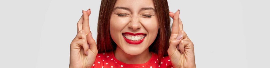 A girl wearing read and red lipstick with crossed fingers