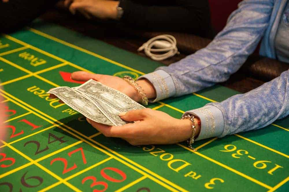 A person is sitting at the casino table and holding money