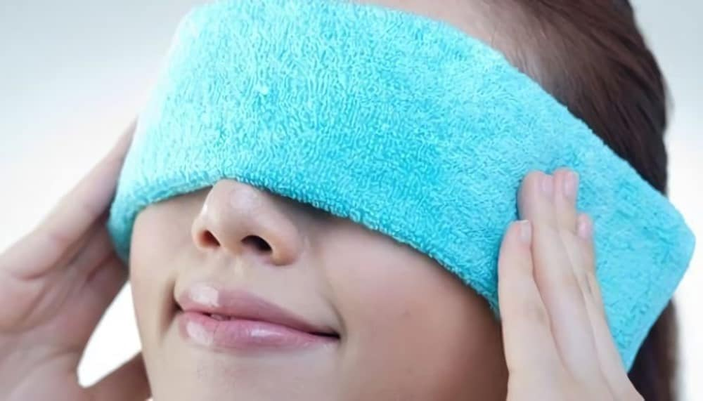 Woman with the blue towel on her eyes is relaxing her eyes