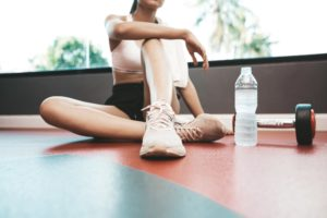 Woman is sitting in the gym and relaxing after exercises