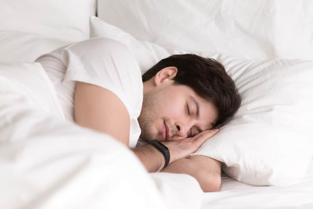 A young man is sleeping wearing fitness bracelet