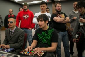 Two players are competing while other attendees are watching during Canada Cup Gaming
