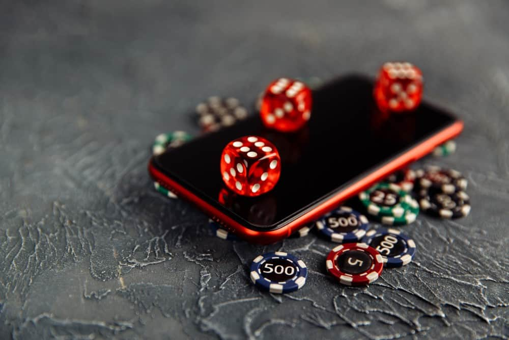 Dices and casino chips are lying on a smartphone
