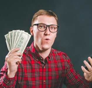 A man is holding a bunch of money he won in a mobile casino app