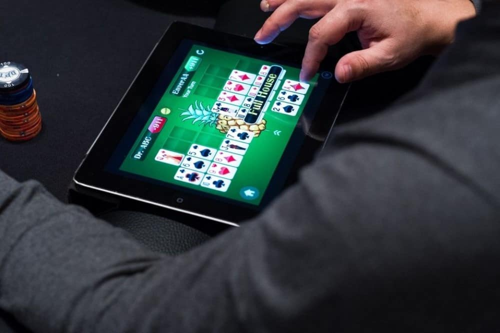 A man is sitting in the casino and playing online casino on his tablet
