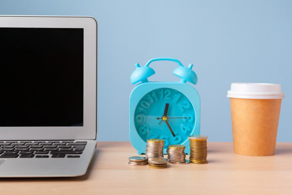 Laptop, clock, coffee cup and piles of coins